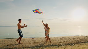 The elder brother is playing with his younger sisters. Running with a kite, girls are catching up with him. A happy stock video footage