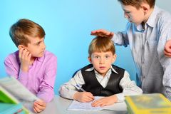 The elder brother teaches his younger brothers and helps to do their homework stock photo