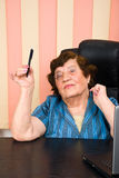 Elder business woman holding a pencil. Elder business woman sitting in chair at office and holding a pencil in her hand,check also Business people Royalty Free Stock Images