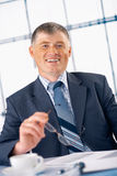 Elder Businessman Holding Glasses. Elder business manager smiling and holding glasses in his hand in the office Royalty Free Stock Image
