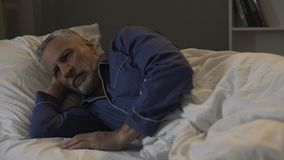 Elder cannot fall asleep, exhausted by bad thoughts and sad memories, insomnia. Stock footage Stock Image