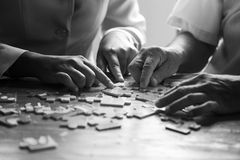 Elder care nurse playing jigsaw puzzle with senior man. In nursing home. black and white Royalty Free Stock Photos