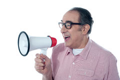 Elder casual man shouting through megaphone. Old person shouting into a big speaker on white background Royalty Free Stock Photos