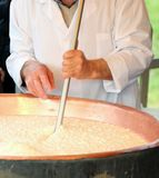 Elder cheesemaker boiling milk into the mixing pot for making ch Stock Images