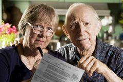 Elder Couple with Bills. Elder Couple at Home with Bills Royalty Free Stock Photo