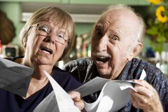 Elder Couple with Bills Royalty Free Stock Photos