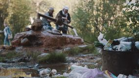 Elder couple filling bottles from rusty pipe wellspring in woods full of trash. Mountain tourist trails stock video footage