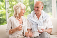 Elder couple holding cups Stock Photography