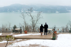 Elder Couple holding each other while standing and staring the cold lake. Greece Stock Photos