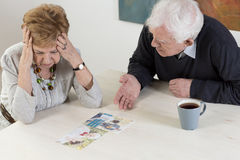 Elder couple's difficult conversation. Depressed women and her husband having difficult conversation stock photo