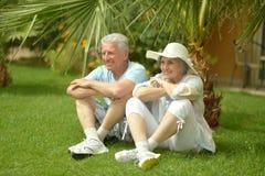 Elder couple sitting near flowers Stock Images