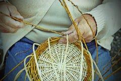 Elder craftsmen create a woven wicker basket Royalty Free Stock Image
