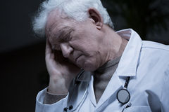 Elder doctor suffering for migraine Royalty Free Stock Photos
