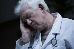 Elder doctor suffering for migraine Royalty Free Stock Photos