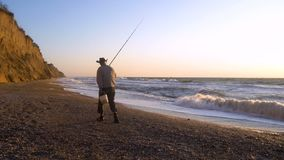Elder Fisherman in Hat fishing at sunrise on the Coast of the Sea at Windy Weather stock video footage