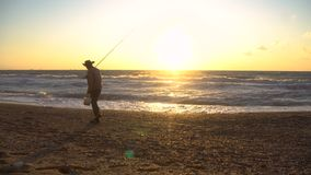 Elder Fisherman in Hat fishing at sunrise on the Coast of the Sea at Windy Weather stock video