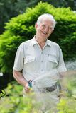 Elder gardener with hosepipe Royalty Free Stock Images