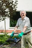 Elder gardener with lawn mower Royalty Free Stock Image