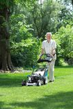 Elder gardener mowing lawn Stock Images