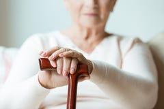 Elder holding walking cane. Elder holding hands on walking cane while sitting on white sofa in nursing home Stock Photography