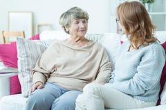 Elder lady with caregiver. Elder lady talking with caregiver in nursing home Stock Images