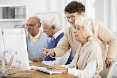 Lady helping her friend. Elder lady with glasses helping her friend with computer issue Stock Photos