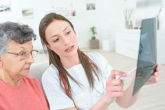 Elder lady looking at x-ray. Elder lady is looking at her x-ray Royalty Free Stock Photo