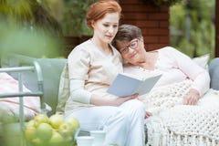 Elder lady resting. Elder lady in glasses covered with blanket resting her head on nurse`s shoulder Stock Photo