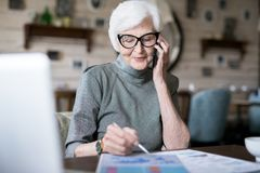Busy senior woman using phone royalty free stock photography