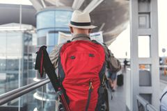 Elder man carrying big bag. Mature tourist is holding red backpack and moving forward. He reading unfolded map. Focus on baggage. Copy space on right side Stock Photo