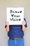 Elder man holding white canvas with the phrase share your voice. concept for elders using internet and social networks. Stock Images