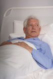 Elder man in hospital bed Royalty Free Stock Photos