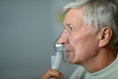 Elder man making inhalation Stock Photos