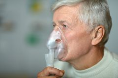 Elder man making inhalation Royalty Free Stock Images
