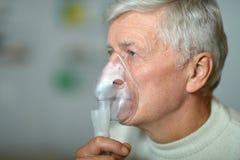 Elder man making inhalation Royalty Free Stock Images