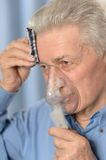 Elder man making inhalation Stock Image