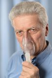 Elder man making inhalation Stock Photography