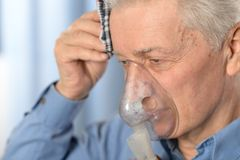 Elder man making inhalationrr Royalty Free Stock Photography