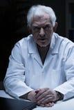 Elder man in medical apron Royalty Free Stock Photos
