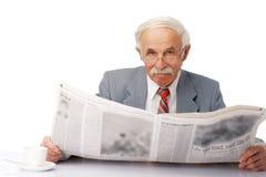 Elder man reading a newspaper. Portrait of an elder happy man reading a newspaper Stock Photo