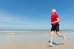 Elder man running at the beach Royalty Free Stock Image