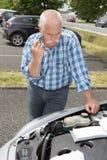 Elder man servicing car at home Stock Images