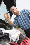 Elder man servicing car at home. Elder man servicing his car at home Stock Photos