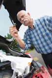 Elder man servicing car at home. Elder man servicing his car at home Royalty Free Stock Images
