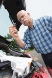 Elder man servicing car at home Royalty Free Stock Images