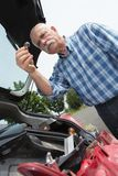 Elder man servicing car at home. Elder man servicing his car at home Royalty Free Stock Image