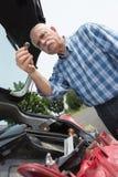 Elder man servicing car at home Royalty Free Stock Image