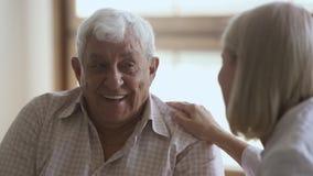 Elder man talking to mature doctor caregiver telling complaints laughing