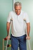 Elder man using a crutches Stock Image