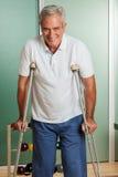 Elder man using a crutches Royalty Free Stock Photos